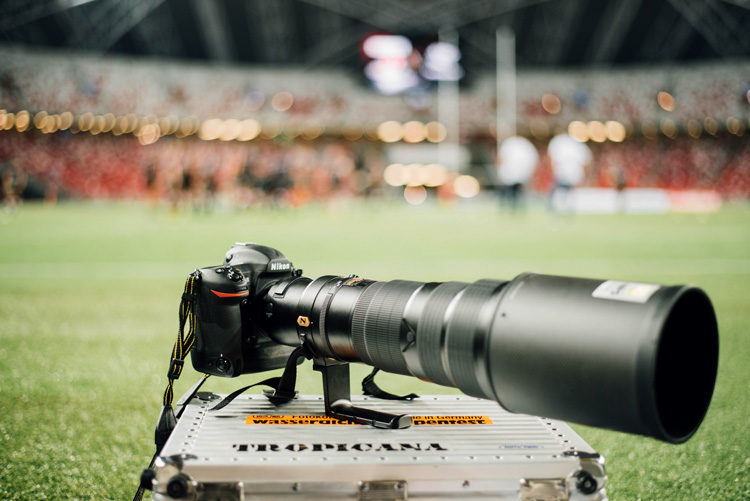 a high end digital camera with long lens for sports photography