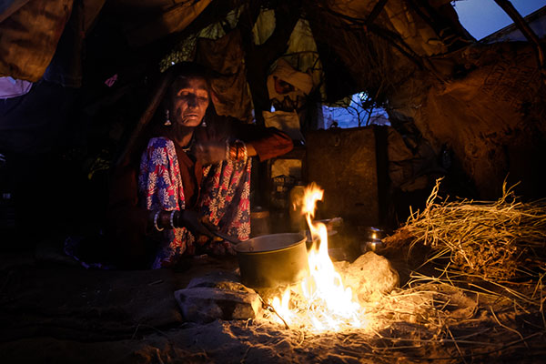 Indian woman early morning preparing breakfast inside a tent during the Pushkar Camel Fair. It is one of the world