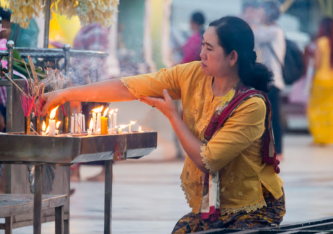 YANGON, MYANMAR: Woman lighting incense in the Shwedagon Pagoda, a famous landmark in Yangon