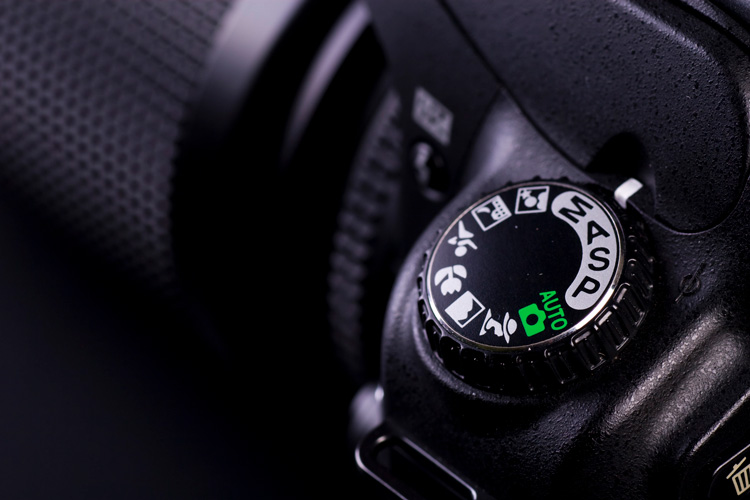 Close up of camera mode settings button on a Nikon camera showing camera modes to choose from
