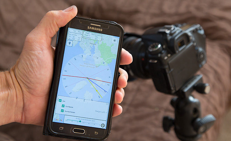 photographer using a smartphone app to assist with his landscape photography