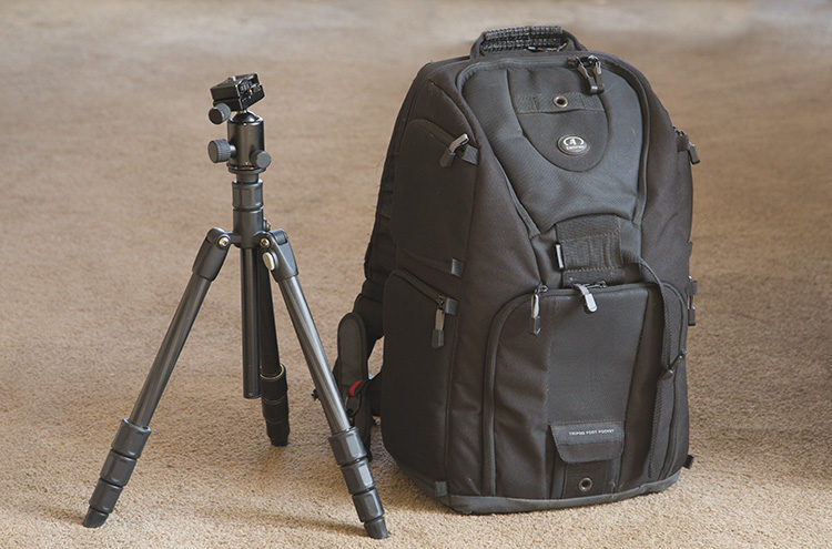 a tripod and camera bag as an example of what to pack for a travel photography vacation