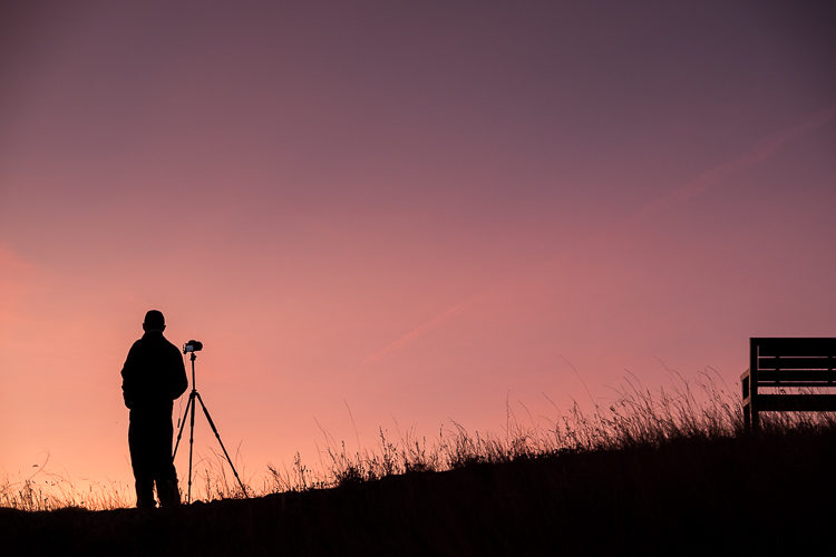 silhouette image of a photographer and bench at sunset, looks best without HDR