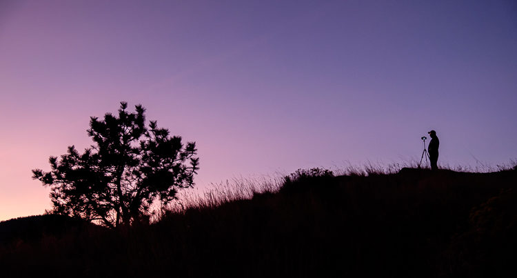 A silhouette photo of a photographer and tripod on a hill during blue hour looks great without HDR
