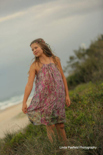 camera shy girl poses in her dress at the beach