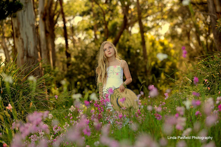 young model posing while surrounded by trees and flowers