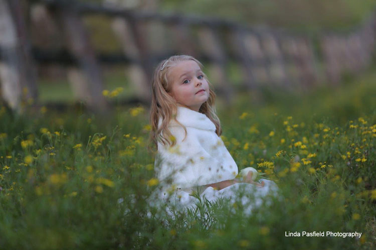 young model poses for her portrait photo while sitting with the flowers