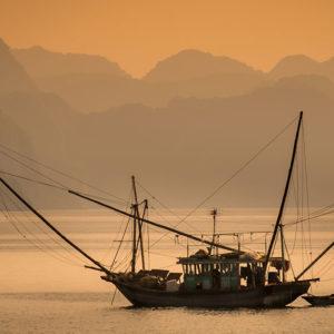 HA LONG BAY, VIETNAM - CIRCA SEPTEMBER 2014: Fishing boat in Halong Bay, Vietnam at sunset.