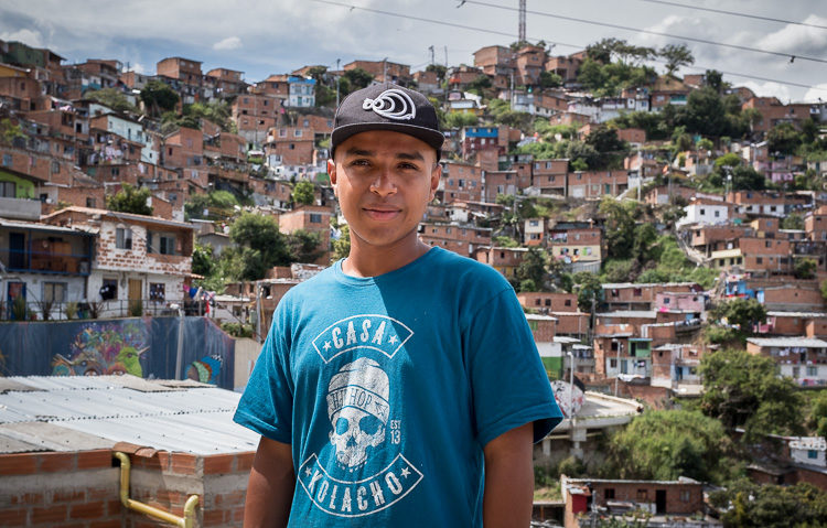 Comuna 13 graffiti tour guide JH stands for a photo with Comuna 13 in the background.