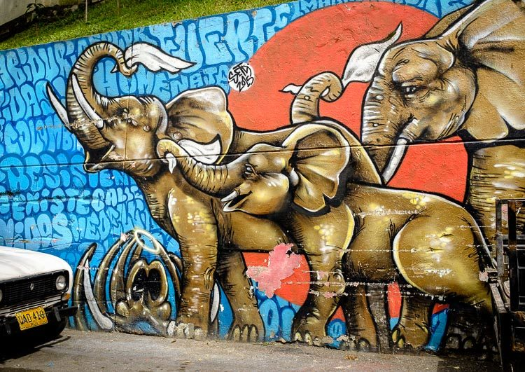 colorful graffiti of three elephants with white flags on a wall in Comuna 13.  It symbolizes the white flags