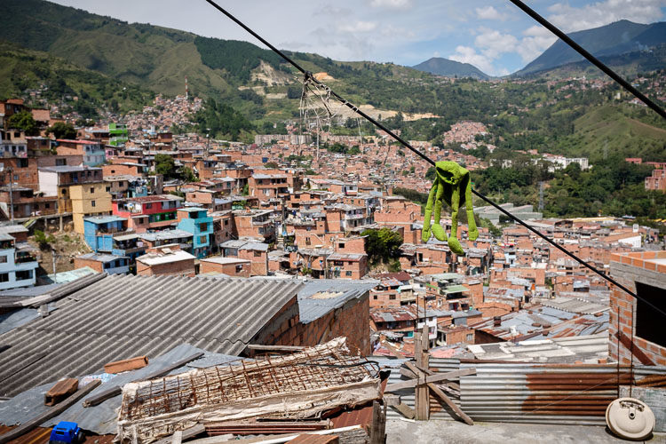 kermit the frog doll dangles on a cable overlooking the roofs of the community below