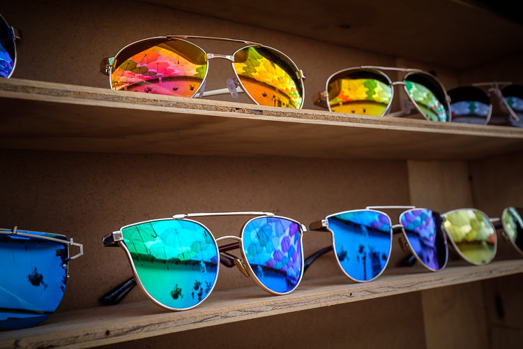 reflections of umbrellas above the street in the sunglass display