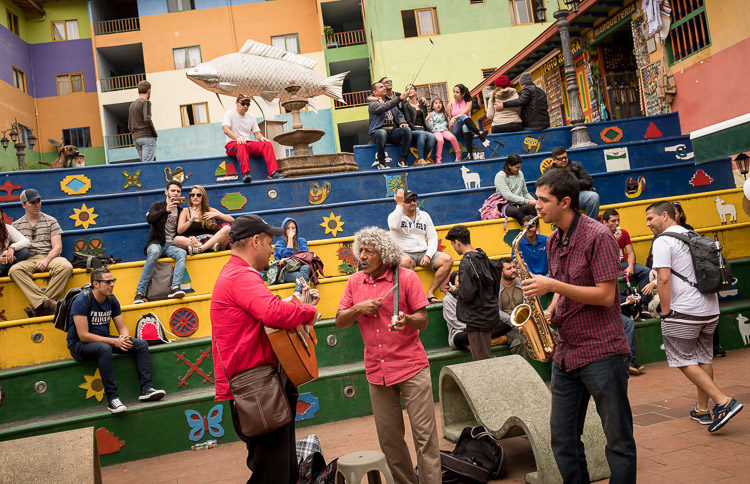 musicians prepare in the space in the square while guests sit in the seats and take pictures of themselves