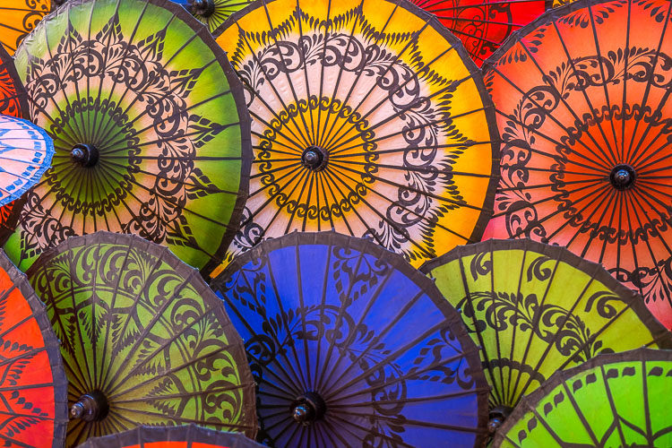 A display of colorful Burmese umbrellas showing blue, green, yellow and orange umbrellas