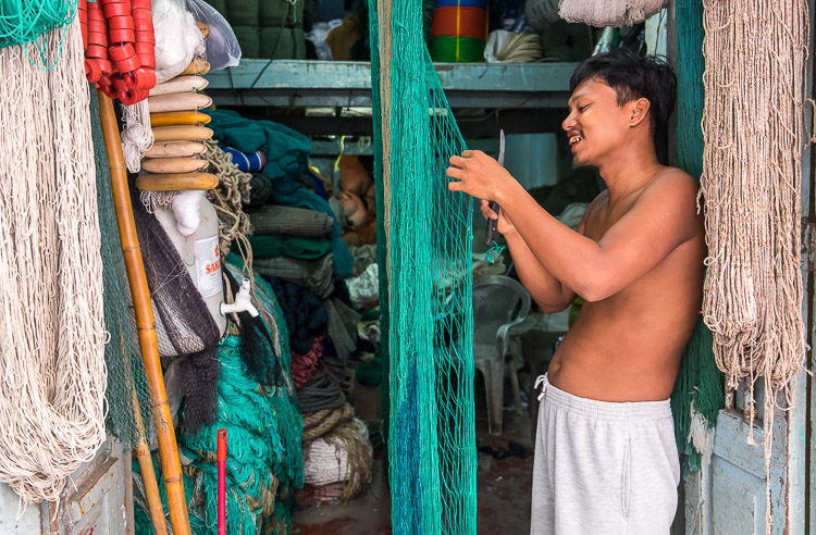 Merchant in the streets of Yangon webbing a fishing net in his storefront