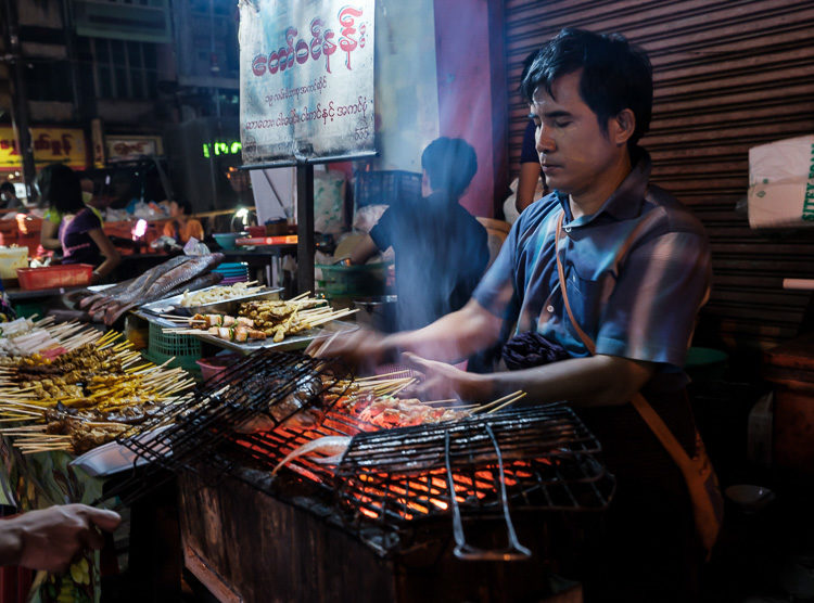 Portrait of Burmese man cooking and selling food in the streets of Yangon at night