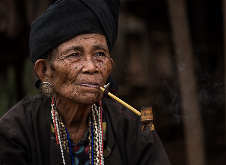 Portrait of an elderly Burmese woman smoking