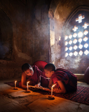 Monks inside a temple reading a book around candlelight on a temple in Bagan.