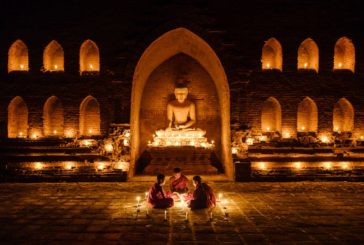 Monks sitting around candlelight on a temple in Bagan, Myanmar