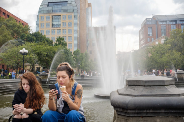 street photography shot of two girls on their mobile phones while sitting at a fountain during a recent trip