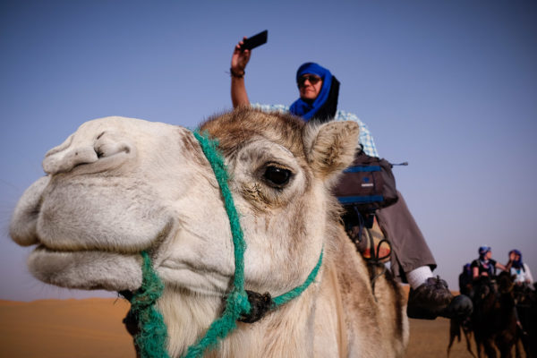 photographer on camel in sahara desert