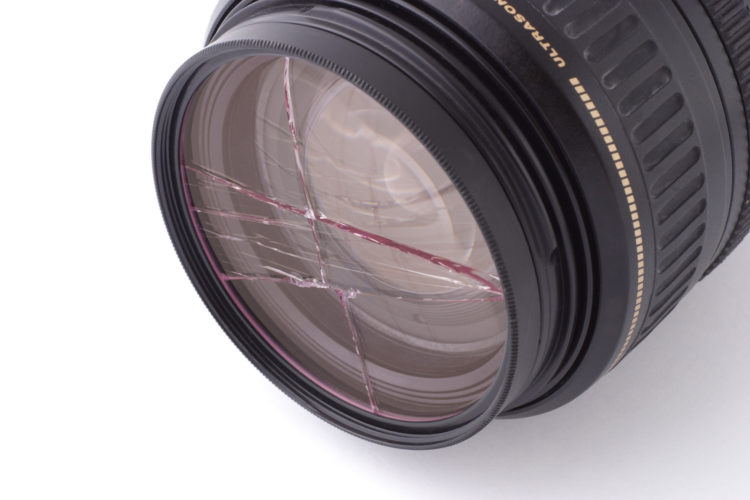 Shattered UV filter fitted on camera lens on white background