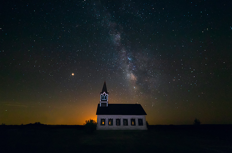 the milky way photographed over rock church