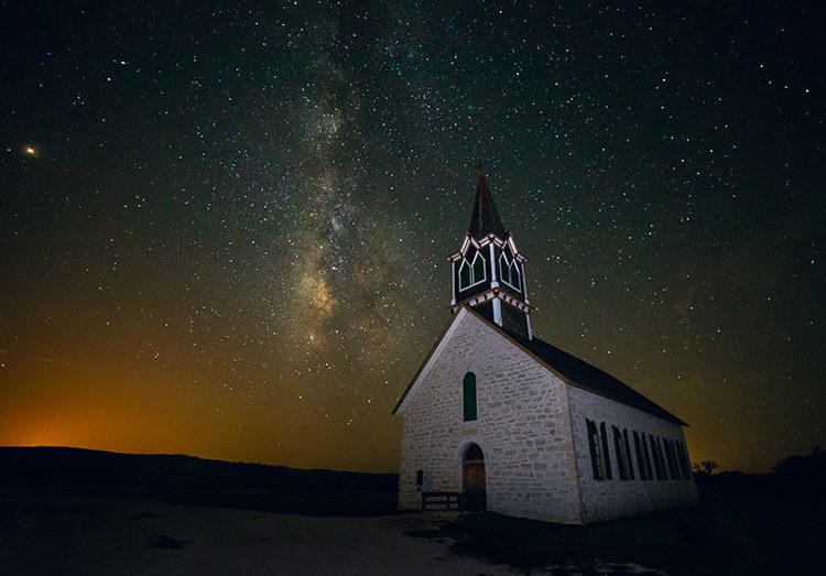 milky way photographed using an old church as foreground
