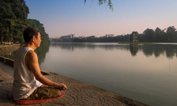A Vietnamese man meditates early morning in the Hoan Kiem Lake, in Hanoi.
