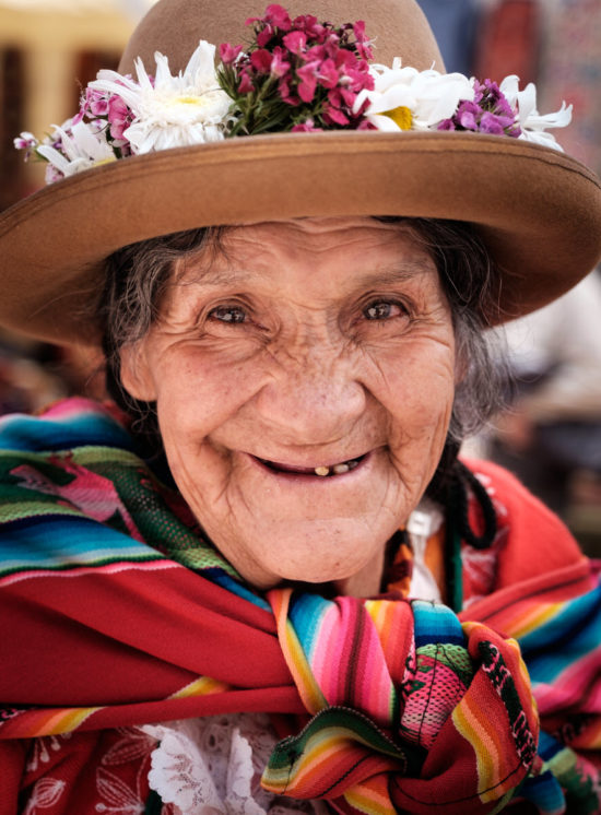 older peruvian woman wearing traditional clothing with vibrant colors smiles for the camera