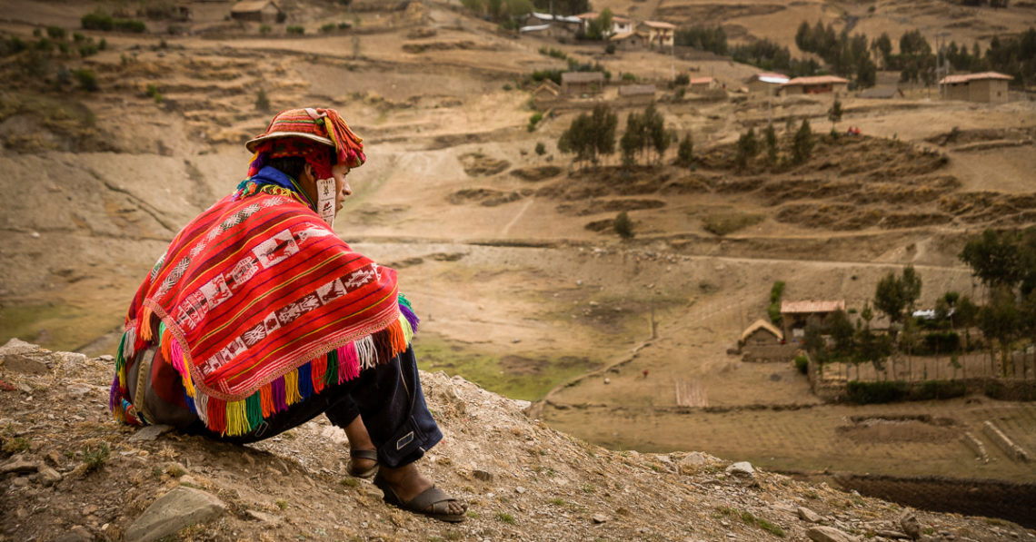 Farmer in remote village, Peru, sits overlooking the land