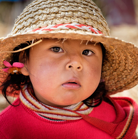 A smiling Peruvian child in a red jacket and hat has her photo taken