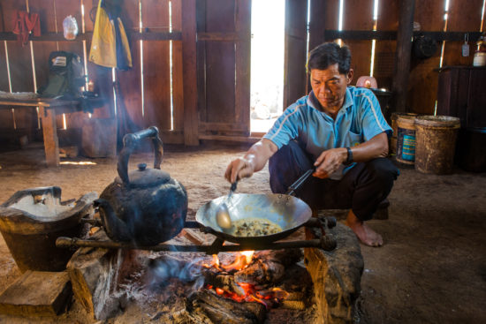 Thai man cooking over an open fire in his house