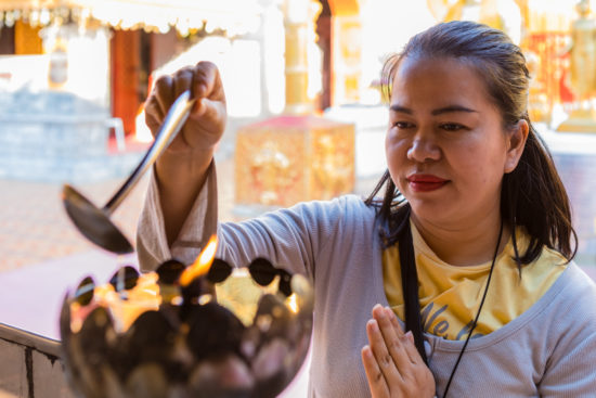 thai woman lighting a candle