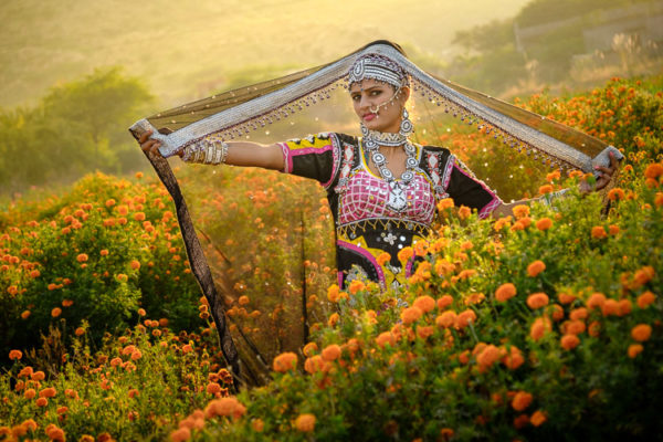 Indian woman in a field of marigolds displaying her scarf
