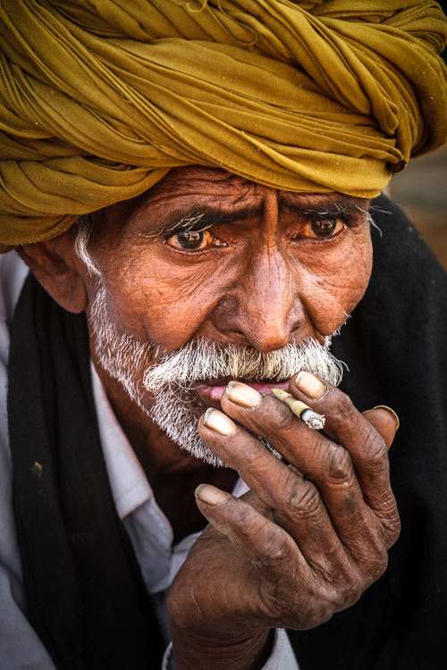 portrait of a man on the street in India smoking a cigarette