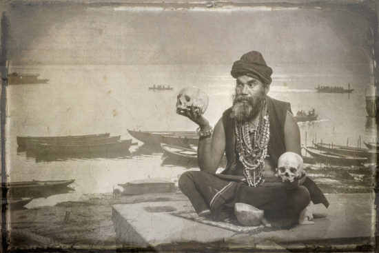 Indian man poses with human skulls in Varanasi India