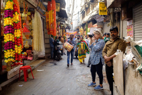 a photographer on tour shoots a street scene in India