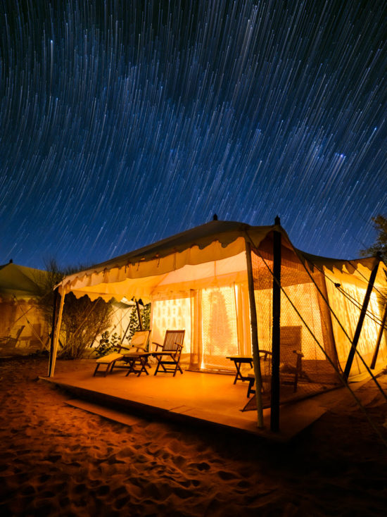 Star trails over a tent in the desert of India
