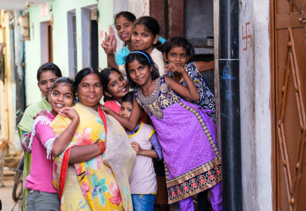 a group of Indian women in traditional dress pose for the camera in a doorway