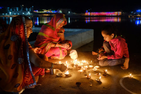 Indian women lighting candles on the edge of a river at night