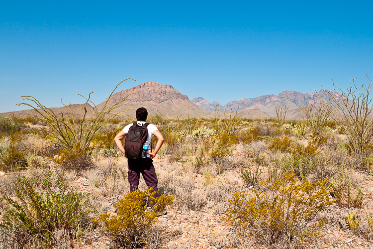 man with backpack in the barren desert - beginner photographer tips