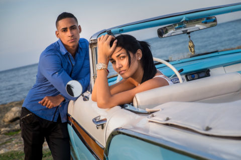 Cuban couple poses on the beach in their classic car
