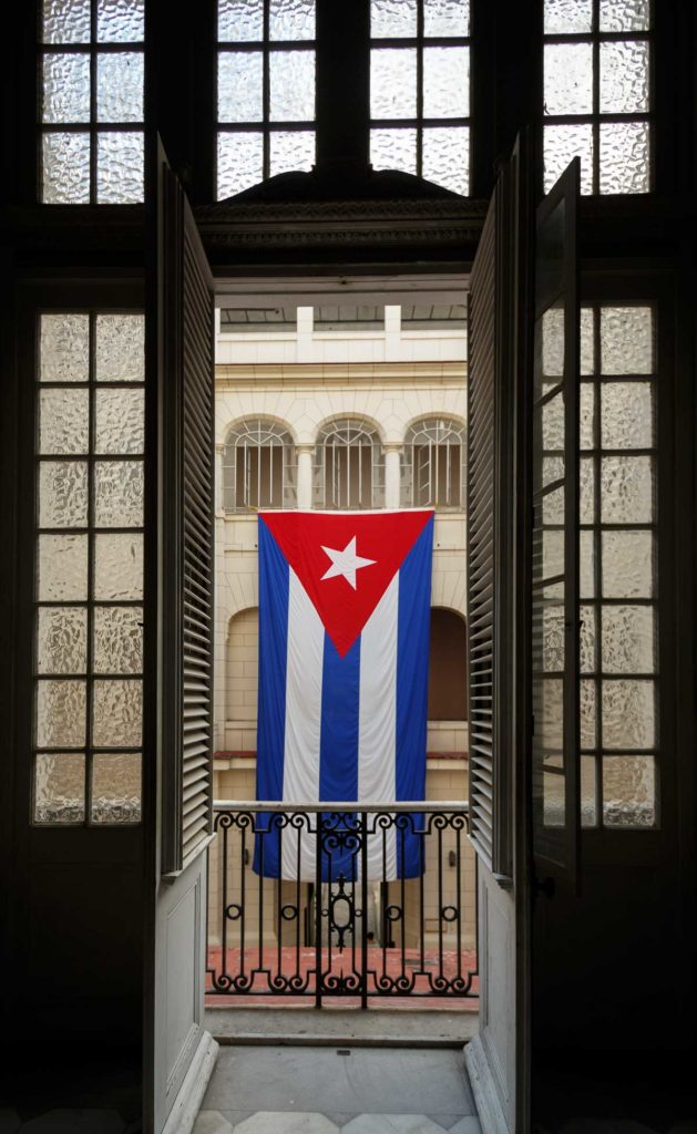 a Cuban flag hangs on a building opposite the open balcony doors in Old Havana Cuba