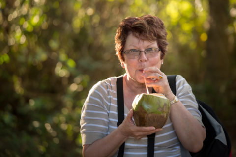Photographer sips rum from a coconut in Cuba while on her photo tour