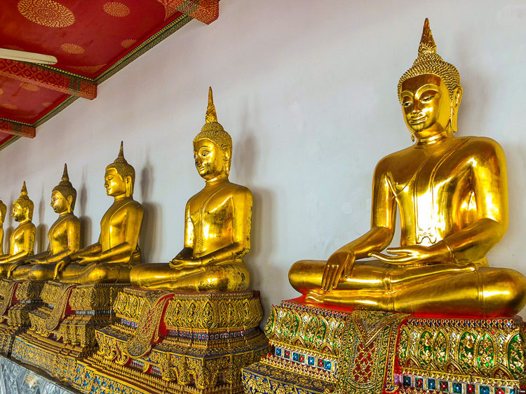 golden Buddha's sit cross legged along the wall at a temple in Thailand
