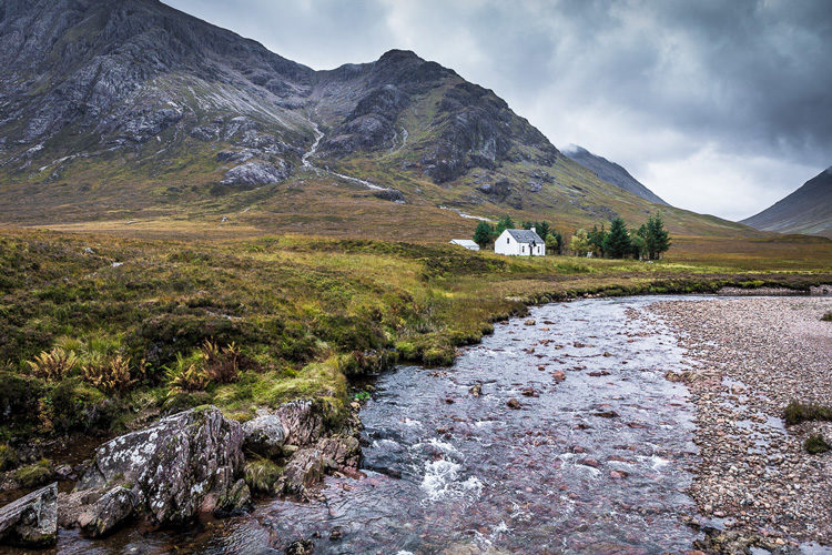 A small cottage next to a stream in the Scottish highlands