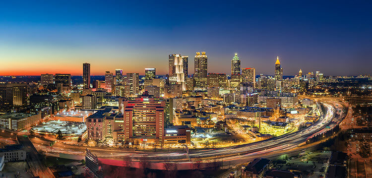 a photo of the Atlanta skyline with car light trails in the foreground. Camera settings of Shutter Speed: 1/5 second; Aperture: f/2.8; ISO 400