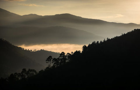 The Bhutan countryside as the sun catches the mist as it rolls in over the valley at sunset
