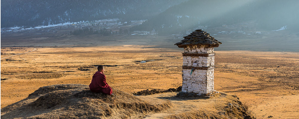 Bhutanese monk sits on a mound in a barren valley lit by the sun